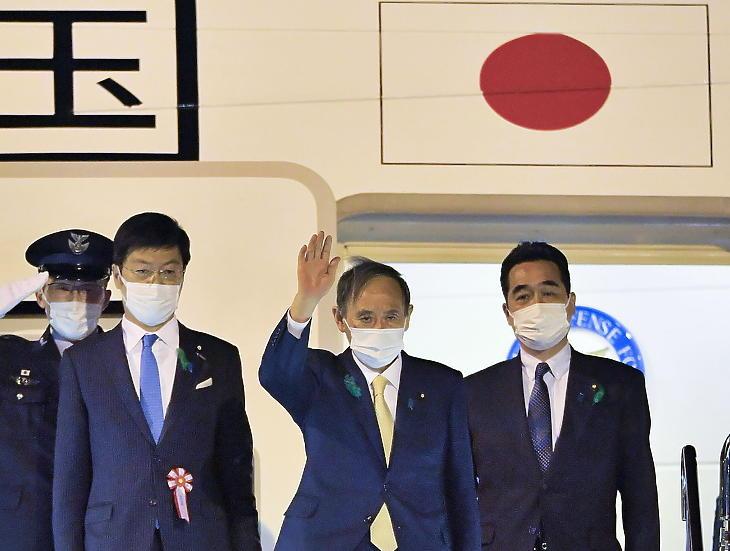 Szuga Josihide japán miniszterelnök integet, mielőtt elindul a repülőtérre a tokiói kormányfői rezidenciáról 2021. április 15-én. (Fotó: MTI/AP/Kyodo News/Goto Szadajuki)