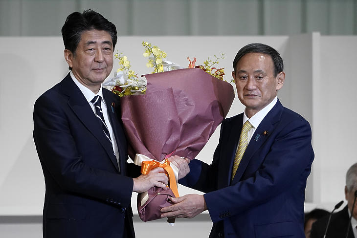 Abe Sindzó japán miniszterelnök (b) virágot nyújt át Szuga Josihide kormányszóvivőnek, miután utóbbi megnyerte a japán kormánypárt, a Liberális Demokrata Párt (LDP) új vezetőjének megválasztására kiírt szavazást Tokióban 2020. szeptember 14-én. Szuga miniszterelnöknek való megválasztása tulajdonképpen már csak formaság volt. (Fotó: MTI/AP pool/Eugene Hoshiko)