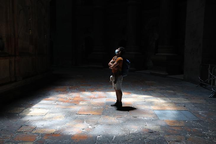 Egy védőmaszkot viselő látogató a jeruzsálemi Szent Sír-templomban 2021. július 15-én. EPA/ABIR SULTAN