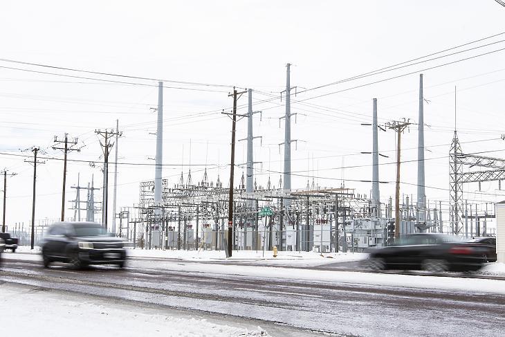 Járművek mennek egy erőmű előtt a texasi Odessában 2021. február 16-án. Mintegy 2,7 millió háztartás maradt áram nélkül Texasban a szokatlan hideg miatt. (Fotó: MTI/AP/Odessa American/Jacob Ford)