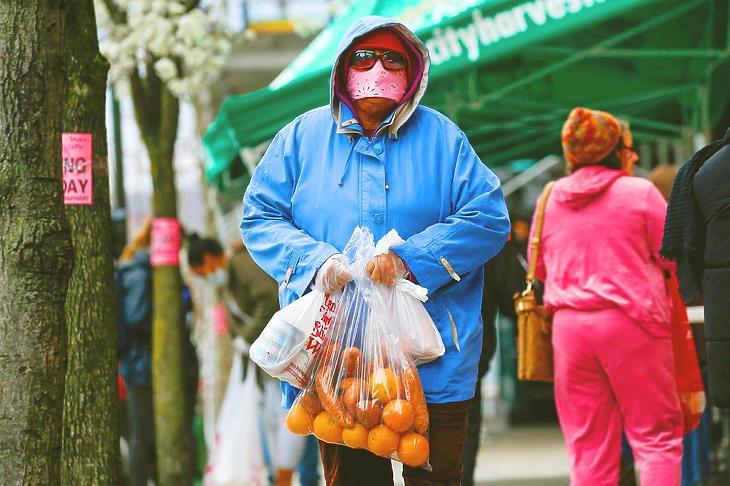 Önkéntes nő visz leselejtezett, de még fogyasztható élelmiszert a rászorulóknak New Yorkban, 2020. március 28-án. (Fotó: AFP)