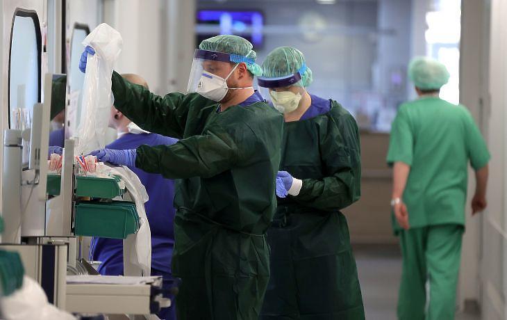 Koronavírusos betegeket ellátó egészségügyi dolgozók egy esseni kórház intenzív osztályán 2020. április elsején. EPA/FRIEDEMANN VOGEL