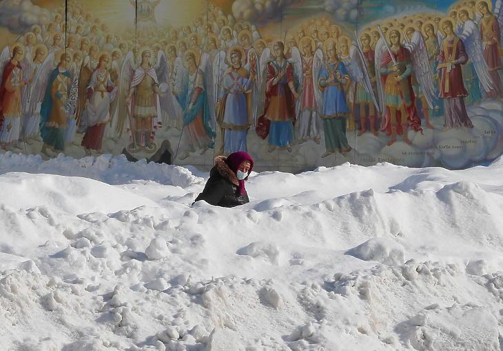 Idős asszony gyalogol egy magas hóval szegélyezett járdán a kijevi Szent Mihály-székesegyház előtt 2021. február 16-án. (Fotó: MTI/EPA/Szerhij Dolzsenko)