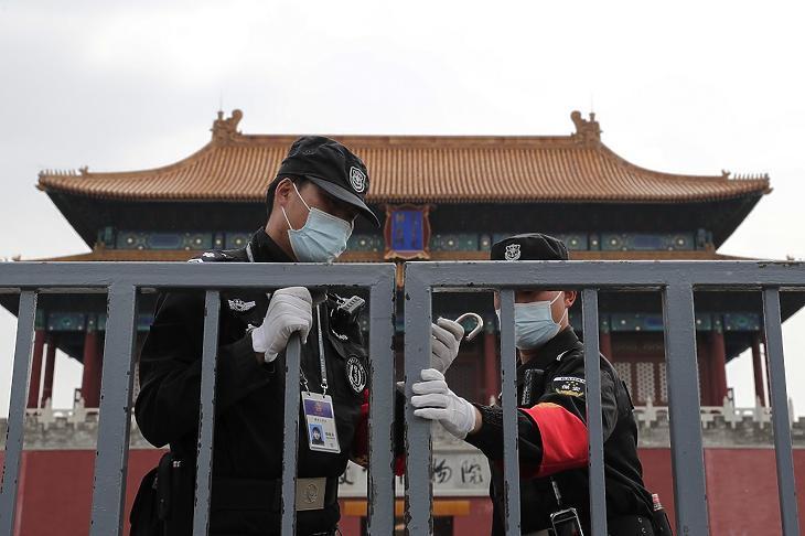 Védőmaszkot viselő biztonsági őrök a látogatók elől lezárt a pekingi Tiltott Város épületegyüttes kapujában 2020. április 19-én, a koronavírus-járvány idején. MTI/AP/Andy Wong