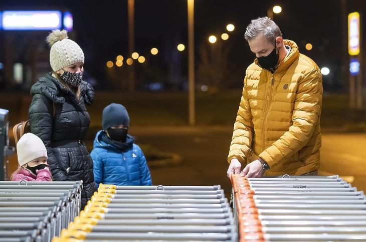Vásárlók egy nyíregyházi szupermarket bevásárlókocsijainál a 19 órai boltbezárás előtt. Új szigorítás egyelőre nincs, ez a maszk is jó lesz. Fotó: MTI/Balázs Attila