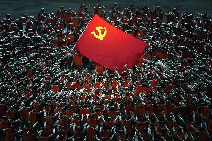 A Kínai Kommunista Párt zászlaja körül a mentők jelmezét viselő szereplők a KKP megalapítása 100. évfordulójának alkalmából rendezett ünnepi előadáson Pekingben 2021. június 28-án. (Fotó: MTI/AP)