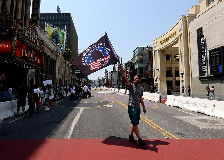 A QAnon csoport zászlaját lengető tüntető 2020. augusztusában Hollywoodban. A csoport egyebek mellett azt terjeszti, hollywoodi színészek gyerekek ellen követnek el bűncselekményeket. Fotó: EPA / Christian Monterrosa