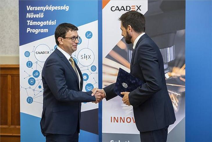 Szanyi Gábor, a Caadex Kft. ügyvezetője (b) versenyképesség-növelő támogatásról szóló szerződést vesz át Magyar Levente államtitkártól (MTI fotó - Mónus Márton)