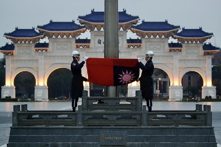 A tajvani díszőrség tagjai a zászlóval Tajpejben (fotó: MTI/AP)