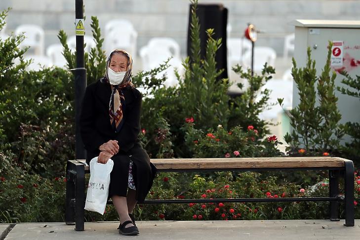 Egy védőmaszkot viselő idős asszony ül egy padon Irán fővárosában, Teheránban 2020. szeptember 24-én.  EPA/ABEDIN TAHERKENAREH