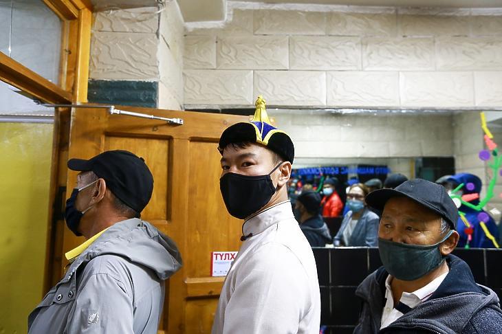 A koronavírus-járvány miatt védőmaszkot viselő emberek várják, hogy leadják voksukat a parlamenti választáson egy ulánbátori szavazóhelységben június 24-én. (Fotó: MTI/EPA)