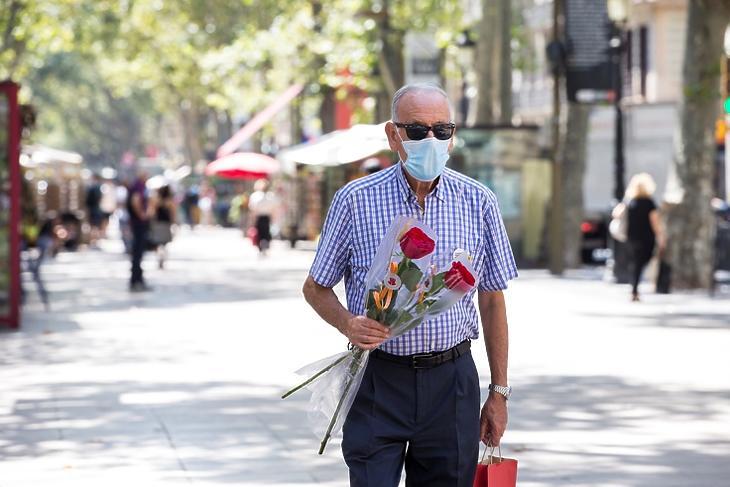 Védőmaszkos, idős ember virággal a kezében Sant Jordi ünnepén Barcelonában 2020. július 23-án. Az ünnepet, amelyen megajándékozzák egymást az emberek, idén három hónapos késéssel tartották meg a járvány miatt.  EPA/Quique Garcia