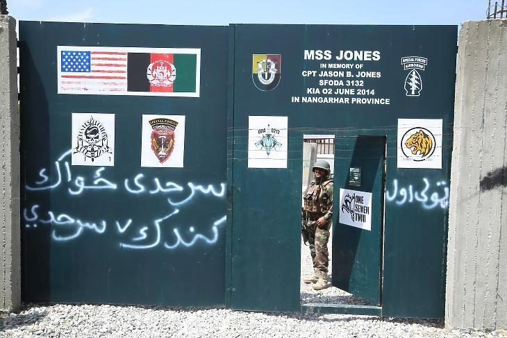 Afgán katona őrködik egy katonai bázison 2021. április 14-én, amelyet korábban az amerikai hadsereg használt. A felirat alapján egy olyan amerikai katonáról nevezték el a bázist, aki 2014 júniusában ütközetben esett el Afganisztánban. Fotó: EPA/Ghulamullah Habibi