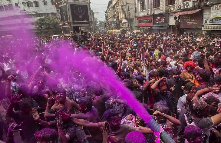 Indiai férfiak és nők táncolnak a hinduk tavaszköszöntő ünnepén, a Holi fesztiválon Gauháti városban 2021. március 29-én. Az évenkénti tavaszünnepen színes porfestéket hintenek, vagy színesre festett vizet öntenek egymásra az emberek, mivel a hinduk hite szerint a tarka színek távol tartják az ártó szellemeket. Kevesebb mint egy hónappal később napi 300 ezer fölött jár a koronavírussal újonnan megfertőződöttek száma. Fotó: MTI/AP