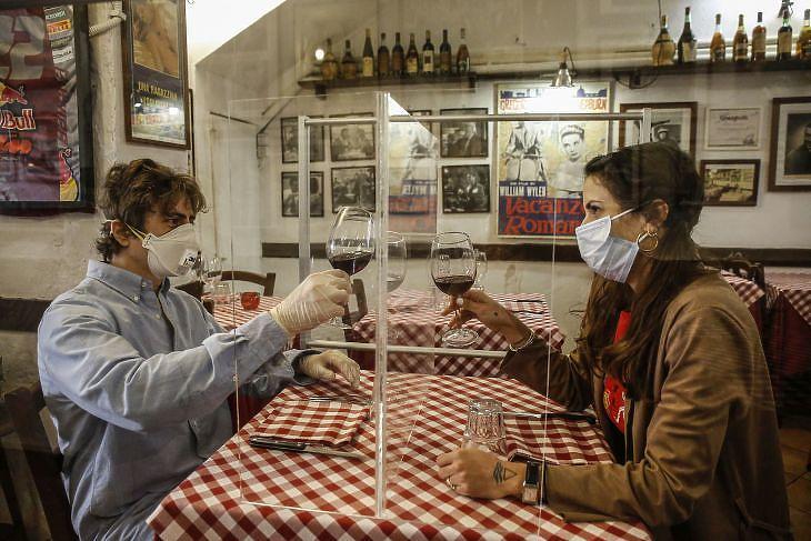 Valerio Calderoni olasz étterem-tulajdonos és felesége, Martina egy plexiüveg-elválasztót tesztel a római Il Ciak étteremben 2020. április 23-án. EPA/FABIO FRUSTACI