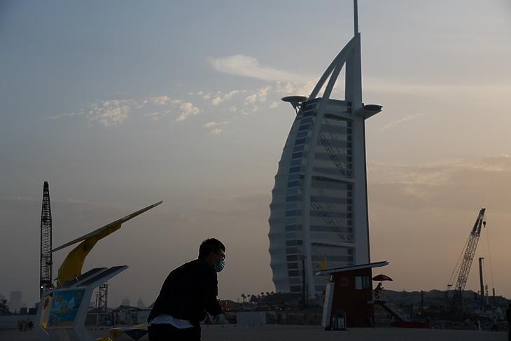 Védőmaszkot viselő turista fényképet készít a dubaji Burdzs al-Arab luxusszállodáról 2020. március 20-án. MTI/AP/Jon Gambrell