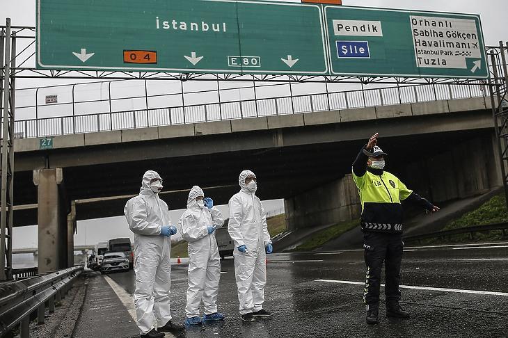 Egy buszt állít meg egy rendőrtiszt, hogy egészségügyi szakemberek megmérjék az utasok testhőmérsékletét Isztambulban 2020. március 29-én. Illusztráció. MTI/AP/Emrah Gürel