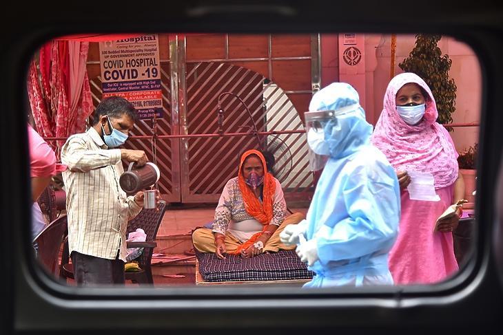 Egy Covid-gyanús beteg kap oxigénkezelést egy szikh szentélyben Delhi külvárosában 2021. május 10-én. EPA/IDREES MOHAMMED