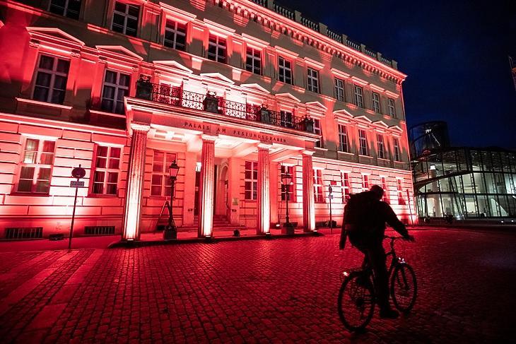 Biciklis a pirosan kivilágított Palais am Festungsgrabennél Berlinben 2020. június 22-én. A világítás a járvány miatti korlátozások nyomán nehéz helyzetbe került rendezvényszervezők problémáira hívta fel a figyelmet. EPA/OMER MESSINGER