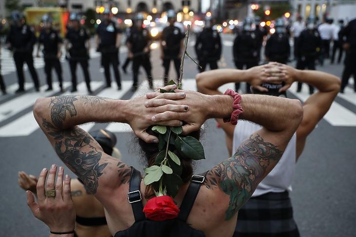 A George Floyd halála miatt tiltakozó tüntetők térdelnek rendőrök előtt, mielőtt a kijárási tilalom megsértése miatt őrizetbe veszik őket New Yorkban 2020. június 3-án. MTI/AP/John Minchillo