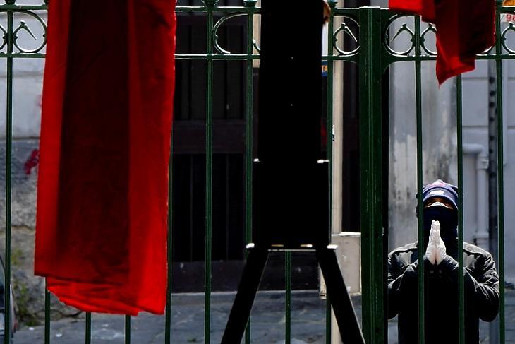 Imádkozó férfi egy bezárt templom előtt Nápolyban 2020. április 10-én. EPA/CIRO FUSCO