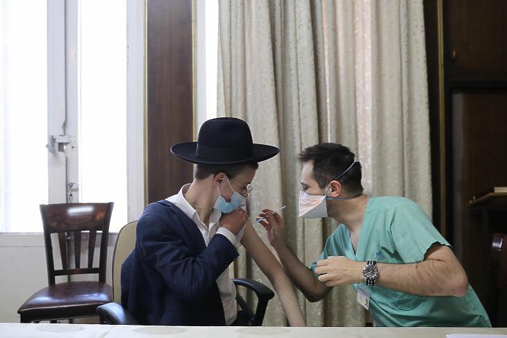 Ultraortodox zsidó fiú megkapja a koronavírus elleni vakcinát az Ichilov Egészségügyi Központban a Tel-Avivtól keletre fekvő Bnei Brakban 2021. február 11-én. Illusztráció. (Fotó: MTI/EPA/Abir Szultan)