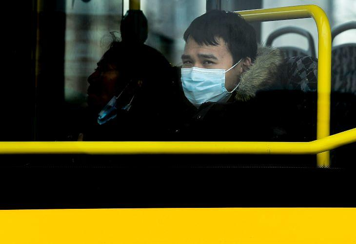 Védőmaszkot viselő utas egy csaknem teljesen üres buszon Berlinben 2020. április 15-én. EPA/FILIP SINGER