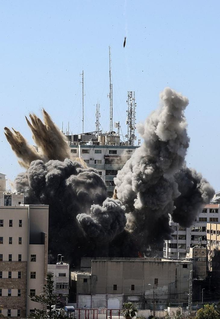 Izraeli légicsapás nyomán megsemmisül egy épület, amely otthont adott az AP amerikai hírügynökség és az al-Dzsazíra pánarab hírtelevízió helyi irodájának is Gáza városában 2021. május 15-én. A Gázai övezetet uraló iszlamista Hamász szervezet és Izrael között május 10-én este kezdődött rakétaháború, miután Jeruzsálemben összecsaptak egymással a palesztinok és izraeli biztonsági erők az iszlám - Mekka és Medina után - harmadik legszentebb helyén, az al-Aksza mecsetnél. MTI/AP/Mahmud Hams