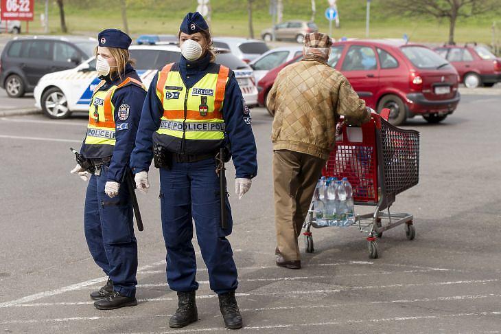 Rendőrök járőröznek egy győri bevásárlóközpont parkolójában a kijárási korlátozás alatt 2020. március 30-án. (Fotó: MTI/Krizsán Csaba)