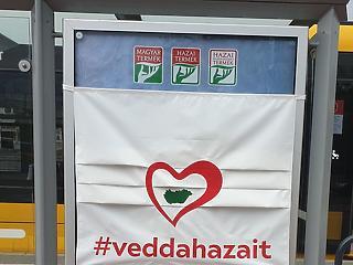 Szájmaszkkal fedett citylight posztereken hirdetik a magyar árut