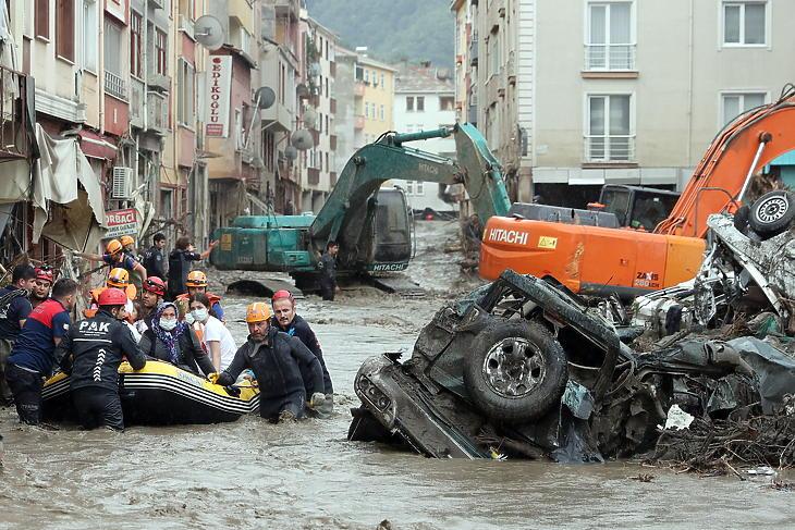Mentőalakulatok tagjai menekítik ki otthonaikból az embereket a heves esőzések nyomán bekövetkezett áradás és földcsuszamlás sújtotta Kastamonuban, Ankarától északra 2021. augusztus 12-én. (Fotó: MTI/EPA/Anadolu/Mehmet Kaman)