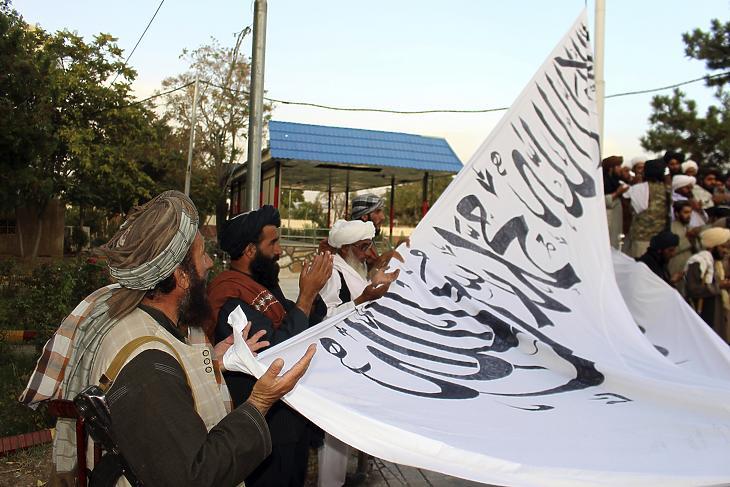 Az afgán kormányerők ellen küzdő tálib harcosok imádkoznak, miközben felvonják zászlajukat a délkelet-afganisztáni Gázni tartomány kormányzójának háza előtt a tartomány azonos nevű székhelyén 2021. augusztus 15-én. (Fotó: MTI/AP/Gulabuddin Amiri)