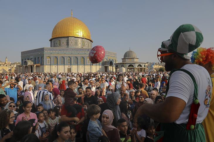Bohóc szórakoztatja a gyerekeket a jeruzsálemi al-Aksza-mecset kertjében álló, arany kupolájú Szikladóm (Omar-mecset) előtt a Templom-hegyen 2021. július 20-án, a mekkai zarándoklatot lezáró, három napig tartó íd al-adha ünnep első napján. (Fotó: MTI/AP/Mahmoud Illean)